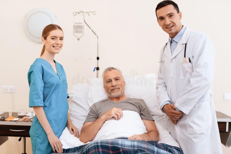 Der alte Mann liegt auf einem Feldbett im medizinischen Bezirk und nahe bei ihm ist eine Krankenschwester und ein Doktor stockfotografie