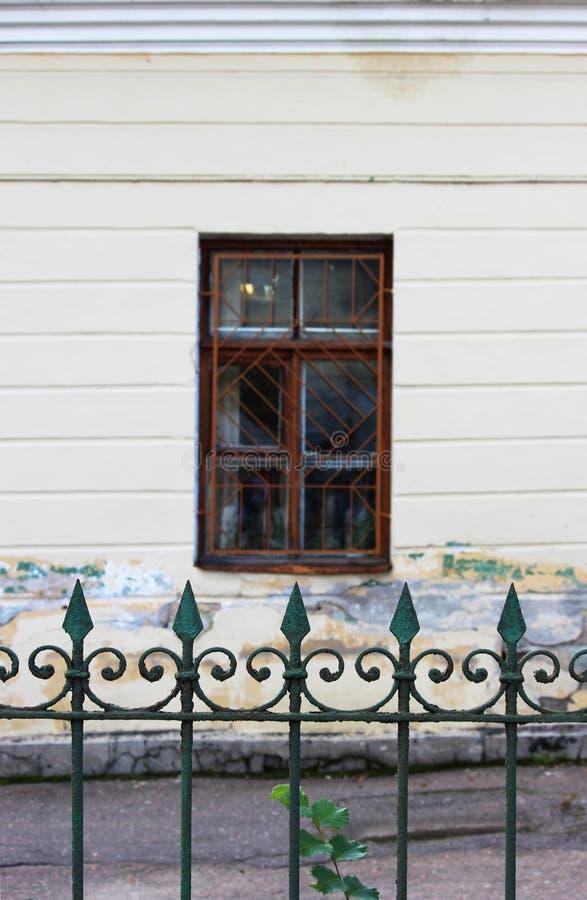 Der alte Metallstadtzaun mit scharfen Punkten wird auf die Oberseite mit grüner Farbe gemalt, die flockig und ein Fenster auf ein lizenzfreie stockfotos