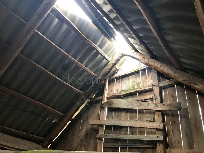 Der alte ruinierte verlassene Dachboden, das Dach vom Innere mit dem Schiefer der Sonne, seine Weise durch die Löcher machend stockfotografie