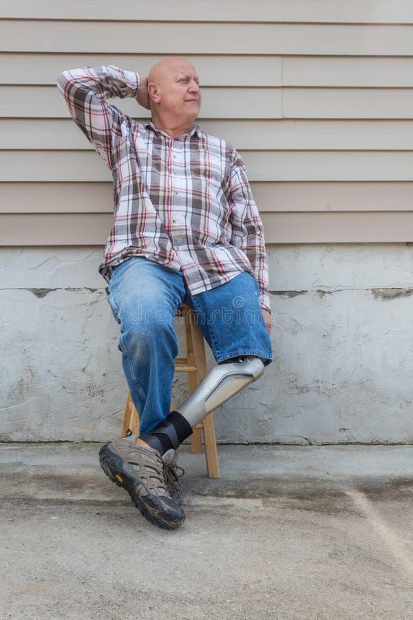 Der Amputiertmann, der auf Schemel mit dem prothetischen gekreuzten Bein sitzt, hatte hinter Kopf lizenzfreies stockbild