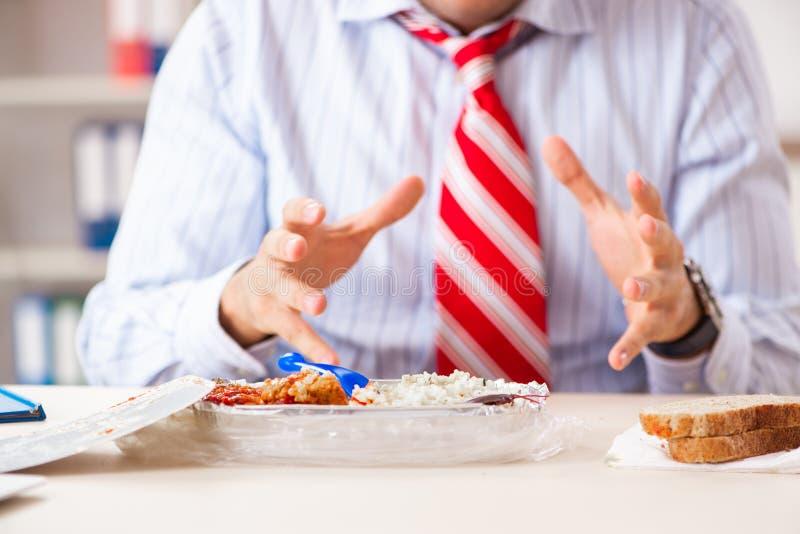 Der Angestellte, der Nahrung mit den Schaben herum kriechen isst stockfotografie
