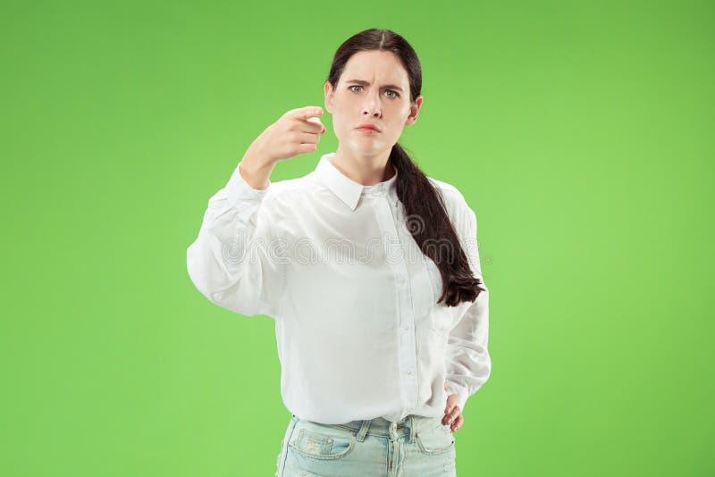 Der anmaßende Geschäftsfraupunkt wünschen Sie und Sie, halbes Längennahaufnahmeporträt auf grünem Hintergrund stockfotos