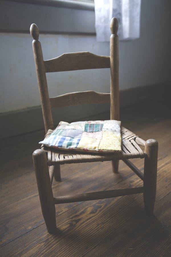 Der antike Stuhl der Kinder mit Steppdecke lizenzfreie stockbilder
