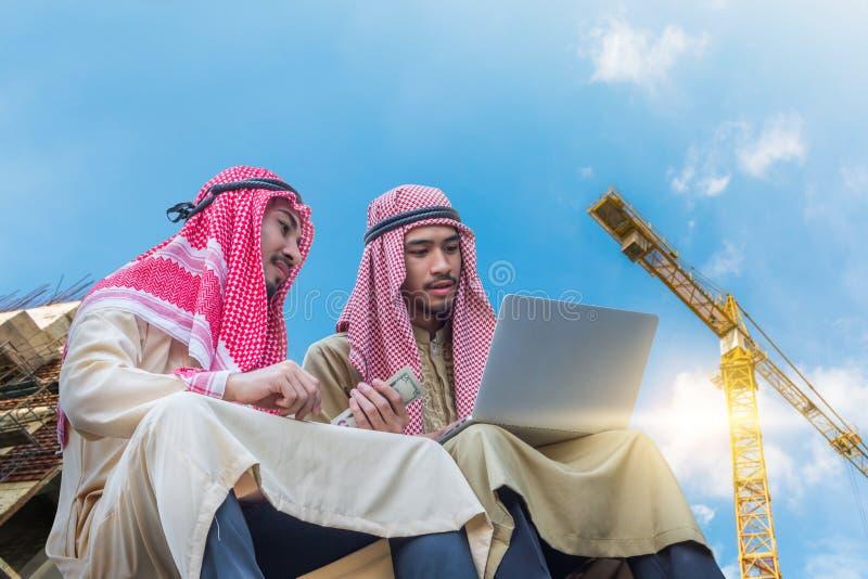 Der arabische Ingenieur, der über kommerzielle Aufgabe spricht und Laptop mit Baustelle und Kranhintergrund verwendet lizenzfreies stockbild