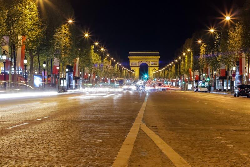 Der Arc de Triomphe in Paris, Frankreich während der Hauptverkehrszeit nachts Traf lizenzfreie stockfotos
