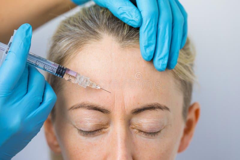 Der Arzt führt die regenerierenden Gesichtsinjektionen zur Glättung der Oberhaut einer Frau durch stockfoto