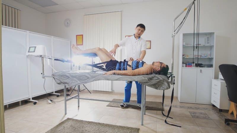 Der asiatische Doktor leitet das Verfahren des Ausdehnens des Dorns, Chiropraktik, asiatische tibetanische Medizin stockfotos