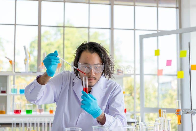 Der asiatische intelligente Mannwissenschaftler, der chemische Flüssigkeit zum Reagenzglas fallenläßt stockbild