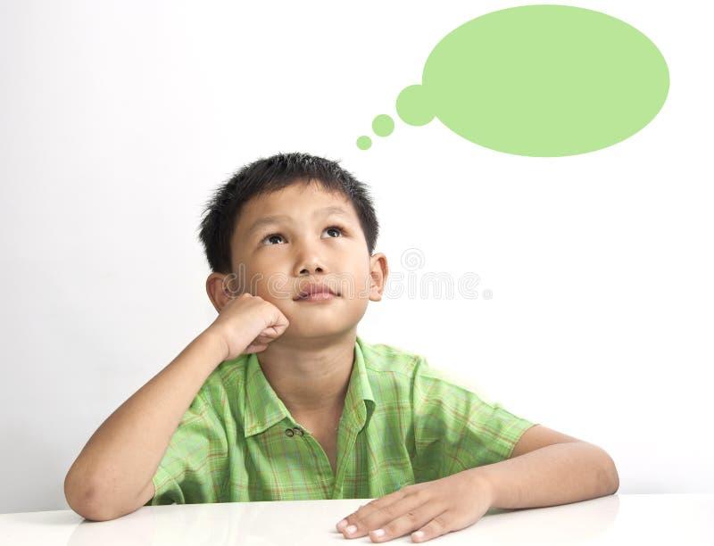 Der asiatische Junge, der auf weißer Tabelle denkt stockfotografie