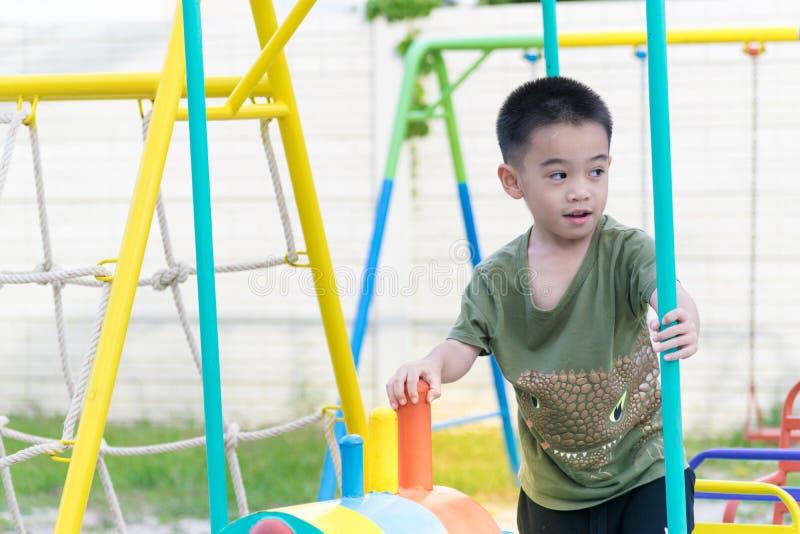 Der asiatische Junge spielt einen Spielplatz auf unscharfem Baum backgroud Dorf von lustigem stockfotografie