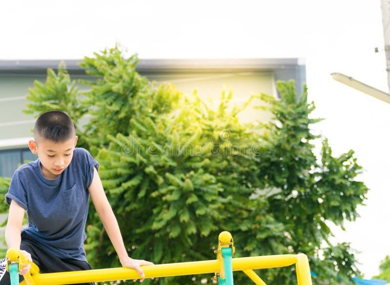 Der asiatische Junge spielt einen Spielplatz auf unscharfem Baum backgroud Dorf von lustigem lizenzfreies stockfoto