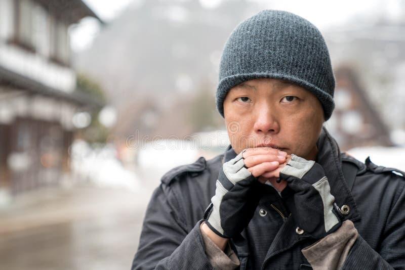Der asiatische Kerl mit Schneehutstarren in die Kamera und in das Denken etwas, Shirakawako-Tal im Schneejahreszeithintergrund stockfotos