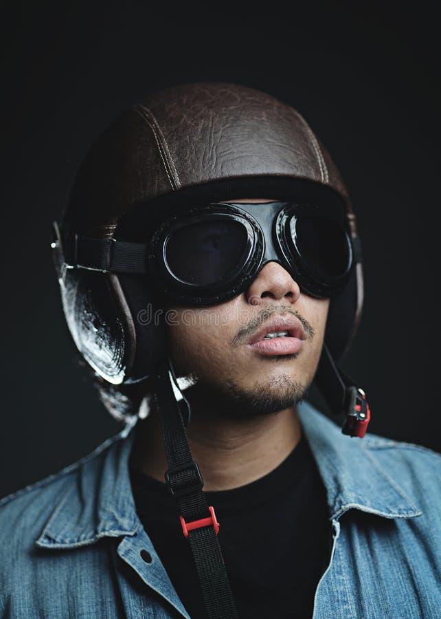 Der asiatische Mann, der Retro- Sturzhelm trägt und googelt lizenzfreies stockfoto