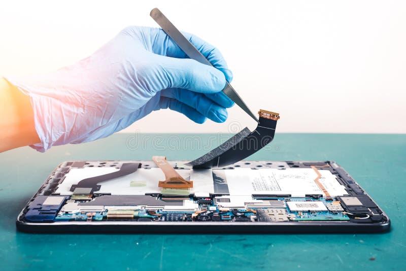 Der asiatische Techniker, der das Smartphone ` s Motherboard im Labor mit Kopienraum repariert stockfotos