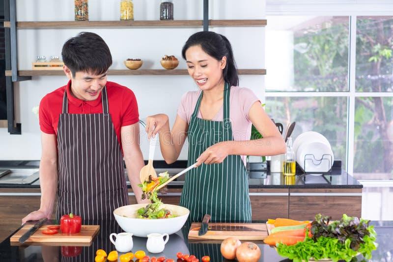 Der asiatischen jungen Paare im Schutzblech, machen zusammen kochen Frauenmischungs-Salatso?e mit Gem?se in der gro?en Sch?ssel e stockfoto