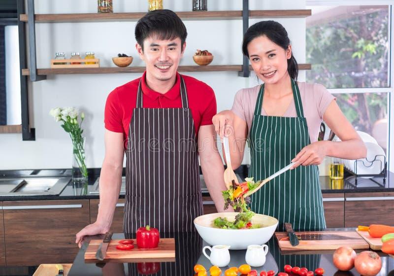 Der asiatischen jungen Paare im Schutzblech, machen zusammen kochen Frauenmischungs-Salatso?e mit Gem?se in der gro?en Sch?ssel stockfotografie