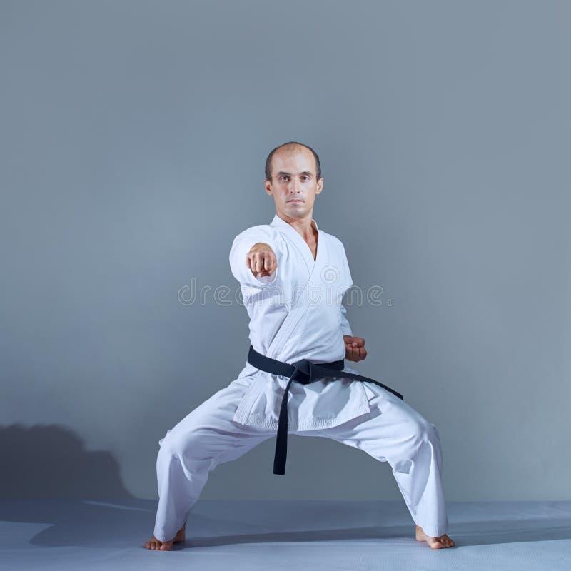 Der Athlet schlägt mit einer Hand im Karategestell gegen einen dunklen Hintergrund stockfotos
