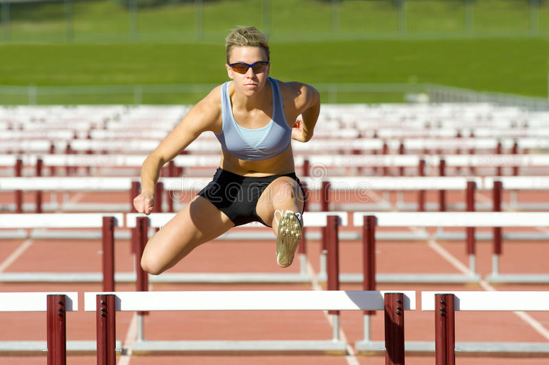 Der Athlet springend über Hürden stockbilder