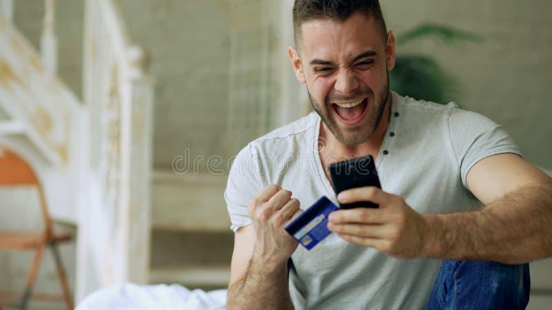 Der attraktive junge Mann mit Smartphone und die Kreditkarte, die im Internet kaufen, sitzen auf Bett zu Hause lizenzfreies stockbild
