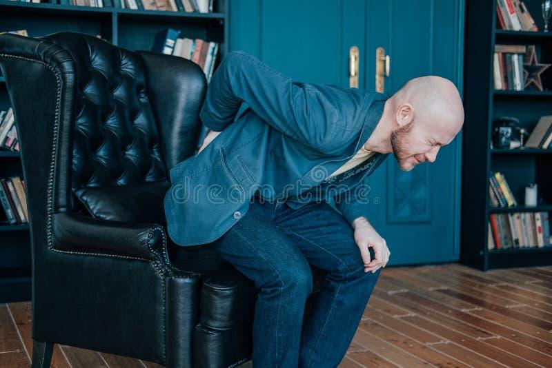 Der attraktive kahle bärtige Mann, der zurück auf seinen, versuchend, von seinem Lederstuhl aufzustehen hält Reiche Leute schreie stockfotos