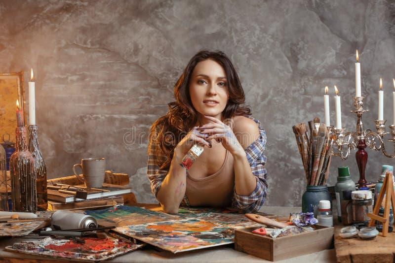 Der attraktive Mädchen Brunette mit dem langen Haar, ist in seiner kreativen Werkstatt, in der sie Skizzen zeichnet und macht füh stockbilder