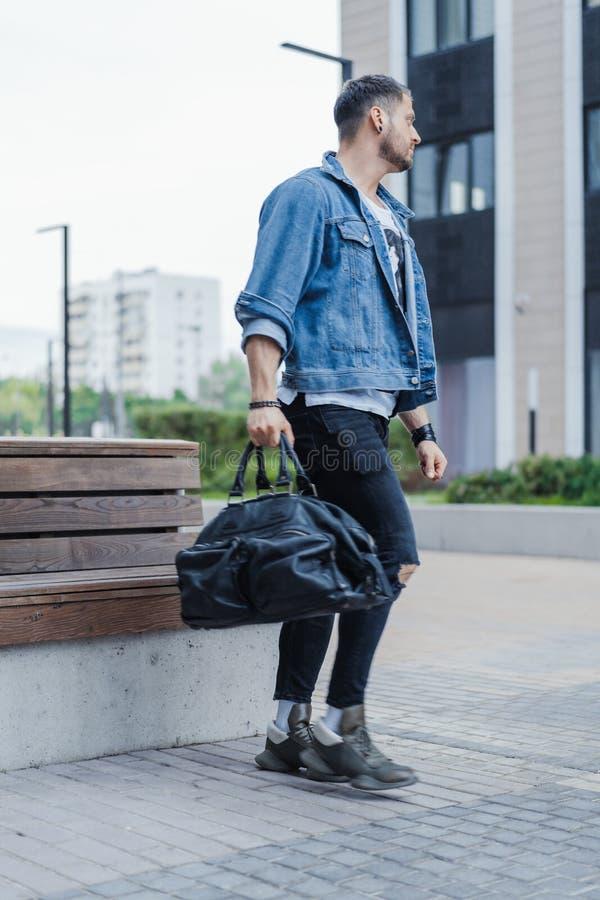Der attraktive Mann, der durch moderne Gebäude überschreitet und Sport hält, bauschen sich stockbild