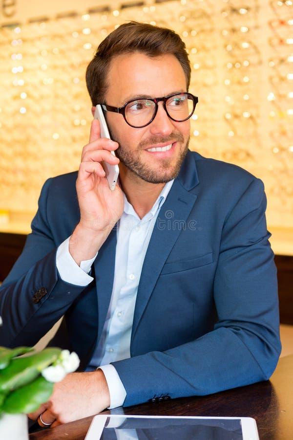 Der attraktive Optiker, der Handy in seinen Gläsern verwendet, kaufen stockbild