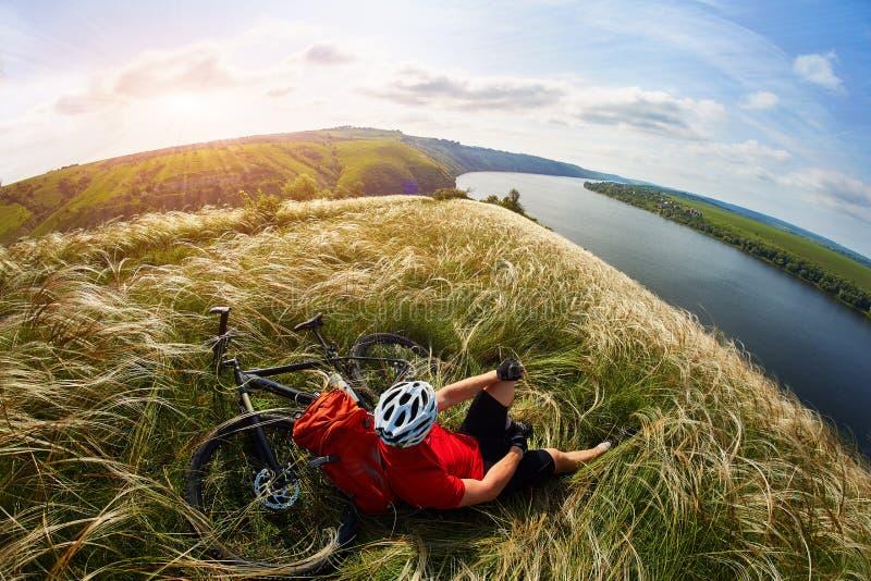 Der attraktive Radfahrer, der auf dem Gras auf der Wiese mit Mountainbike über Fluss sitzt stockfoto