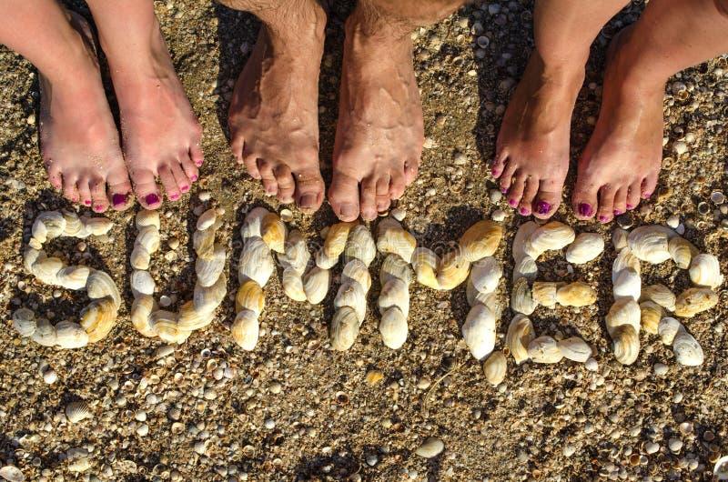 Der Aufschrift SOMMER ausgebreitet von den Oberteilen auf dem Sand lizenzfreie stockfotos