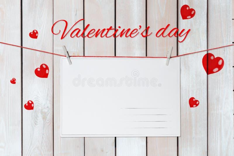 Der Aufschrift Valentinstag ist über der Grußkarte, die durch rote Herzen auf einem weißen hölzernen Hintergrund mit moc umgeben  lizenzfreies stockfoto