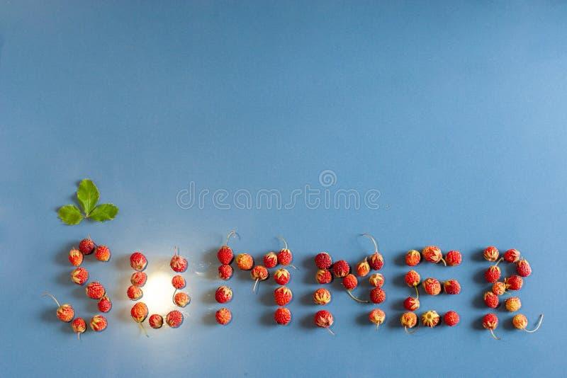 Der Aufschriftsommer gezeichnet mit Erdbeeren auf einem Keramikziegel mit einer Staubbeschaffenheit Ein Blatt über dem Buchstaben lizenzfreies stockbild