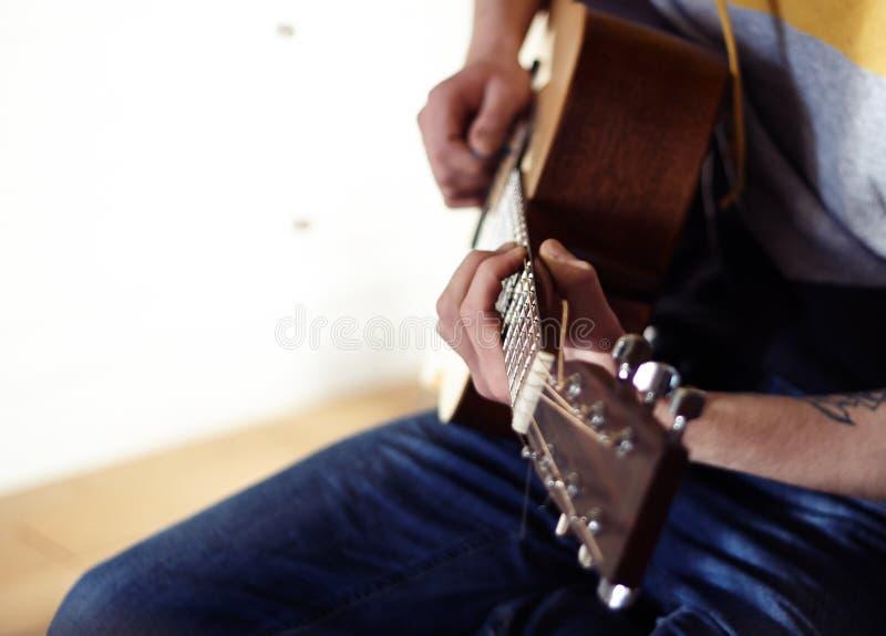 Der Ausführende spielt eine hölzerne Akustikgitarre stockfoto