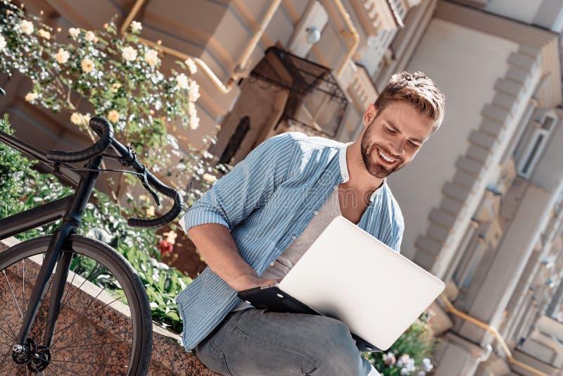 Der Ausgangspunkt aller Leistung ist Wunsch Junger lächelnder Mann, der im Park, seinen Laptop halten sitzt Das Fahrrad stockbilder