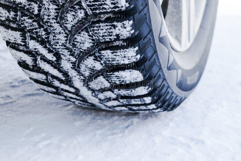 Der Autoreifen im Schneeabschluß oben Autospuren auf dem Schnee Spuren des Autos im Schnee Winterreifen Reifen bedeckt mit Schnee lizenzfreies stockbild