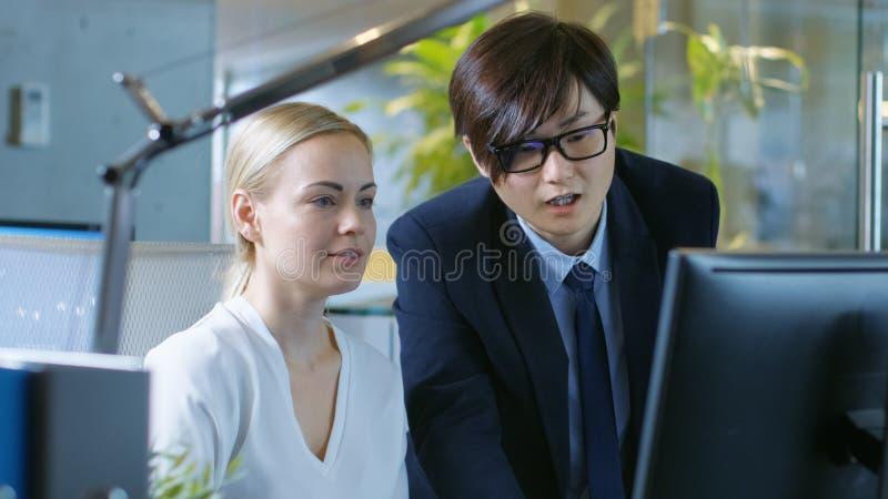 In der Büro-Geschäftsfrau Sitting in ihren Schreibtisch-Gesprächen mit ihrem B stockbild