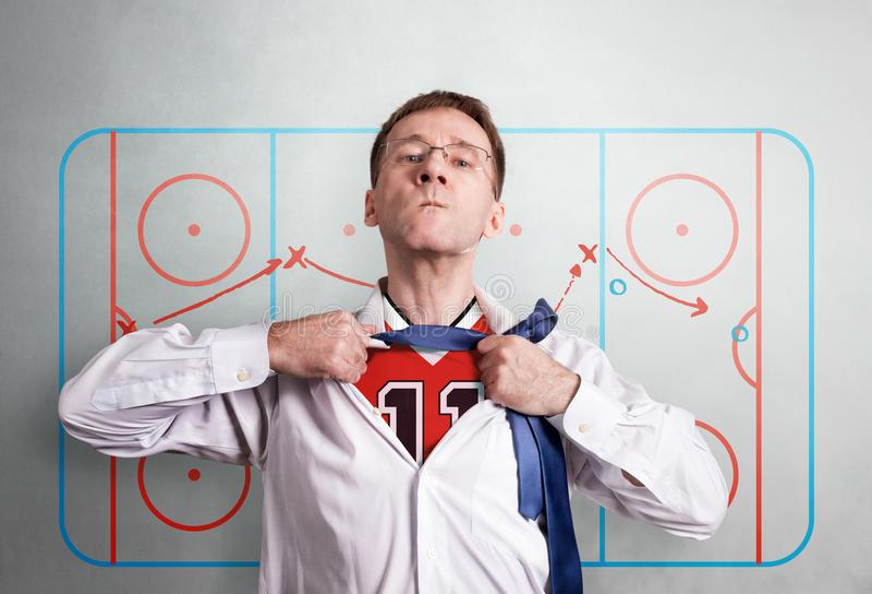 Der Büromann öffnet ein weißes Hemd und zeigt die Hockeysportform Gegen den Hintergrund des Anleitungsentwurfs von halbzeitlich stockfoto