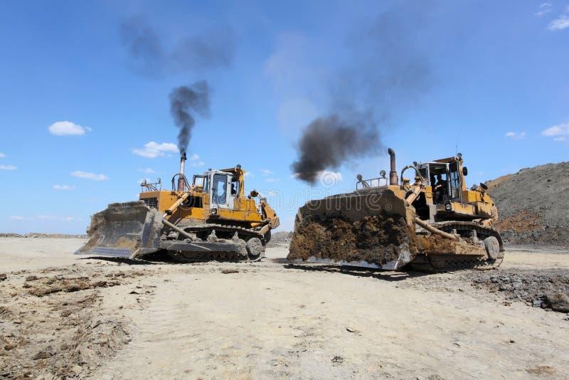 Der Bagger lädt die LKW-Kohle Zwei Planierraupen lizenzfreies stockbild