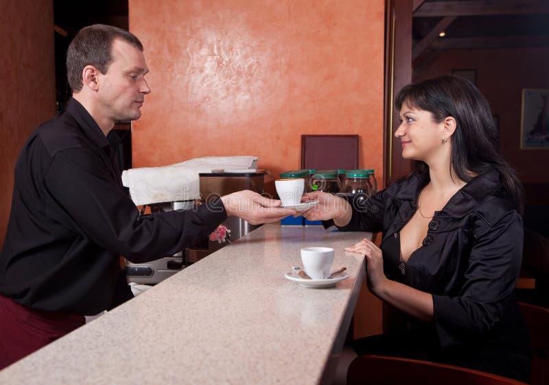 Der Barmixer gibt dem Kellner ein Tasse Kaffee stockfoto