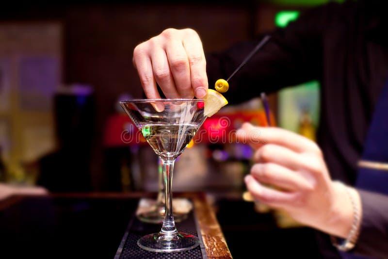 Der Barmixer verziert Stemware mit Martini stockfotografie