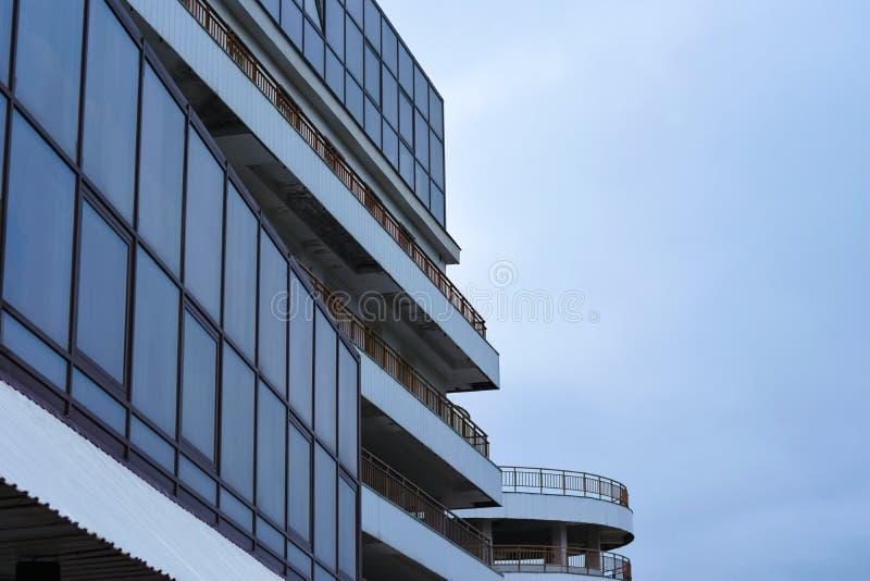Der Bau eines modernen Gebäudes mit Parken von den Glas- und langen Balkonen lizenzfreies stockbild
