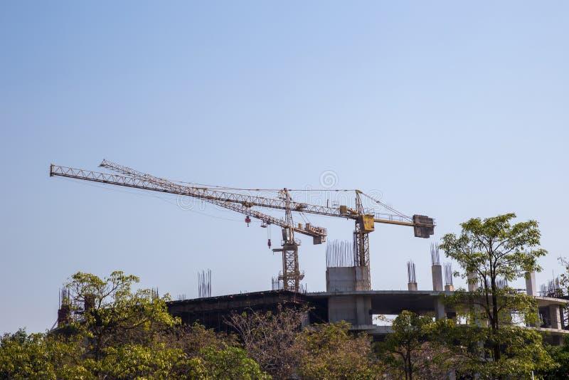 Der Baukran und das Gebäude gegen den blauen Himmel Turmkran an der Baustelle gegen den blauen Himmel stockbild