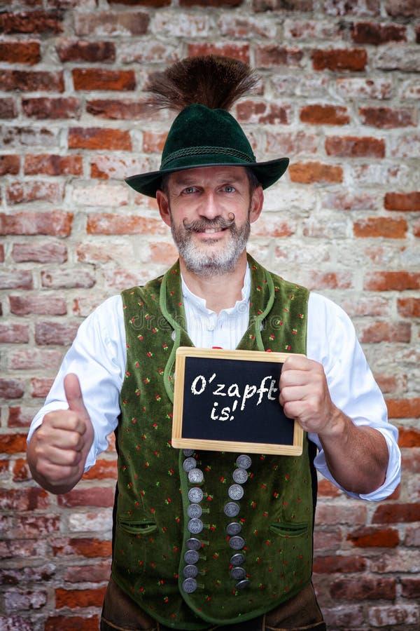 Der bayerische Mann, der Zeichen mit deutschen Wörtern für Bier hält, fließt stockfotos