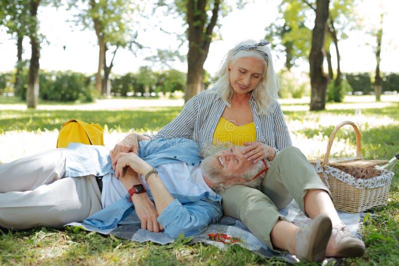 Der begeisterte glückliche Mann, der auf seinen wifes liegt, hüllt ein stockbild