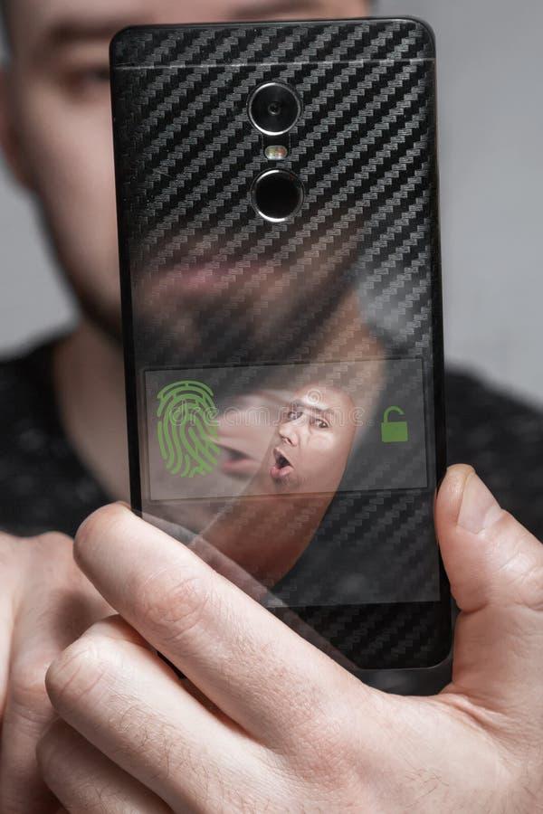Der Benutzer scannt den Finger, um den biometrischen Schutz des Telefons zu führen das Konzept von Gesicht Identifikation stockfotografie