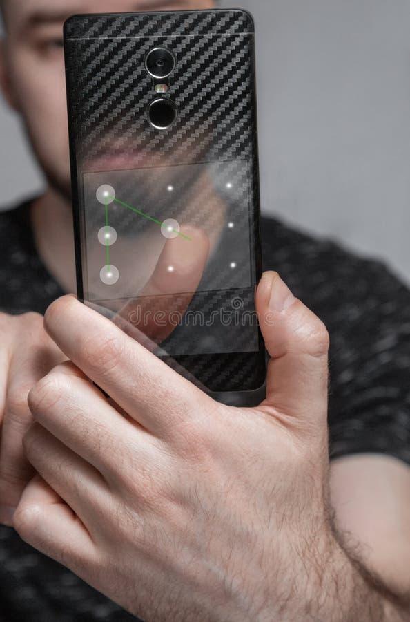 Der Benutzer verwendet den grafischen Schlüssel, um das Telefon zu entriegeln das Konzept der Sicherheit von Personendaten stockfoto