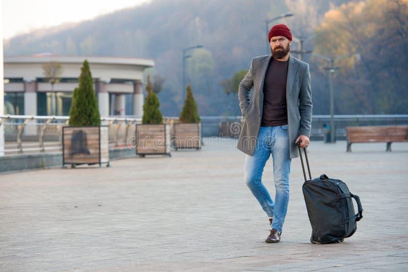 Der bereite Hippie genießen Reise Suchen nach Anpassung Bärtige Hippie-Reise des Mannes mit großem Gepäcktaschenwartung Taxi stockbild