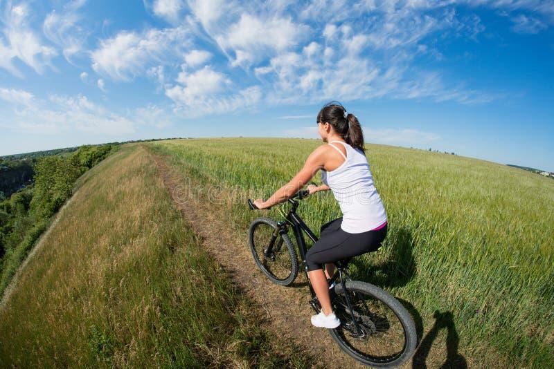 Der Berg, der glückliches sportives Mädchen radfährt, entspannen sich in der sonnigen Landschaft der Wiesen stockbilder