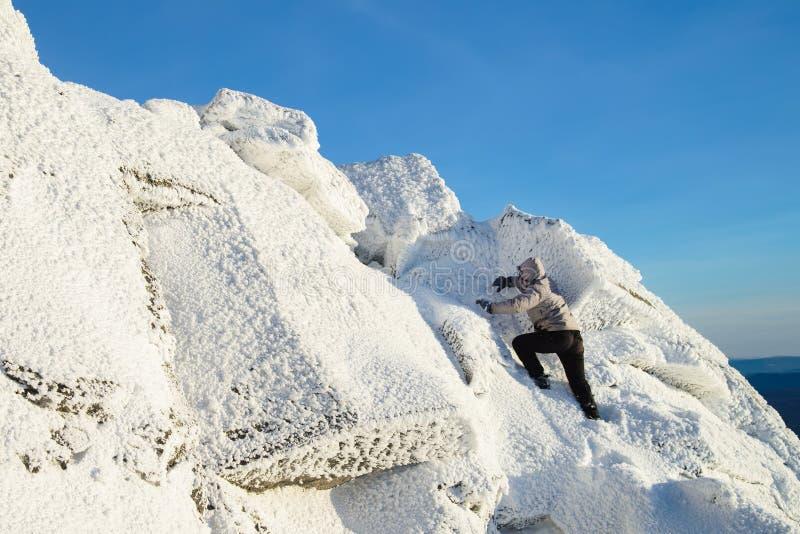 Der Bergsteiger, der das Gebirgsspitzen bedeckt mit Eis und Schnee, Mannwanderer geht an der Spitze des Felsens klettert Stunden  stockbilder