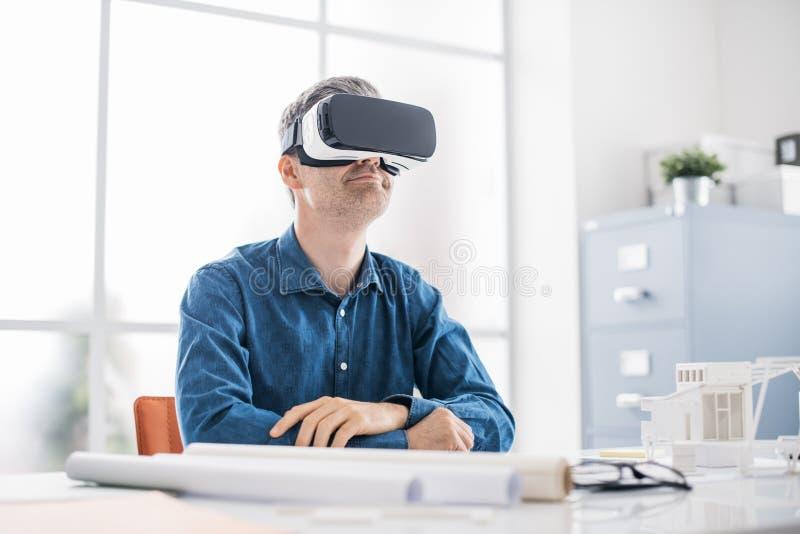 Der Berufsarchitekt, der am Schreibtisch arbeitet und einen VR-Kopfhörer trägt, sieht er eine Schnittstelle der virtuellen Realit lizenzfreie stockbilder