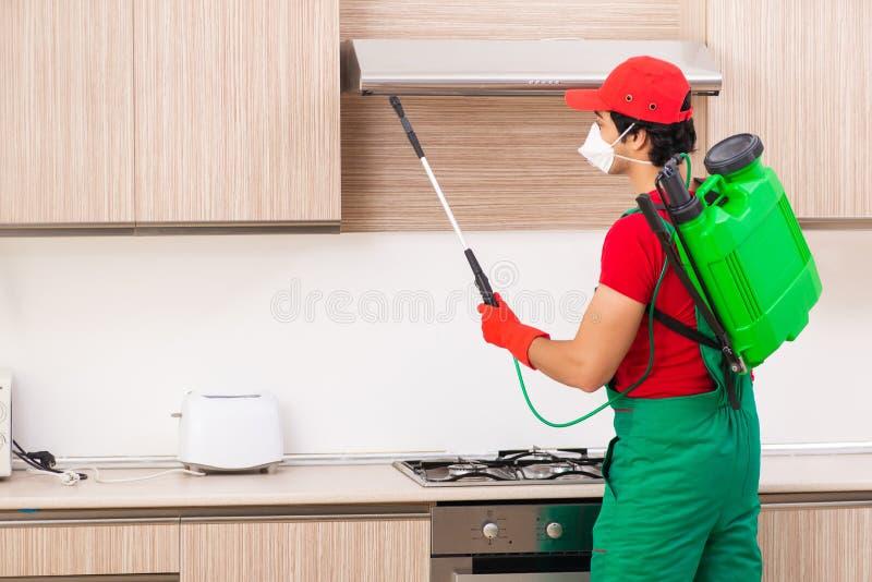 Der Berufsauftragnehmer, der Schädlingsbekämpfung an der Küche tut lizenzfreies stockbild